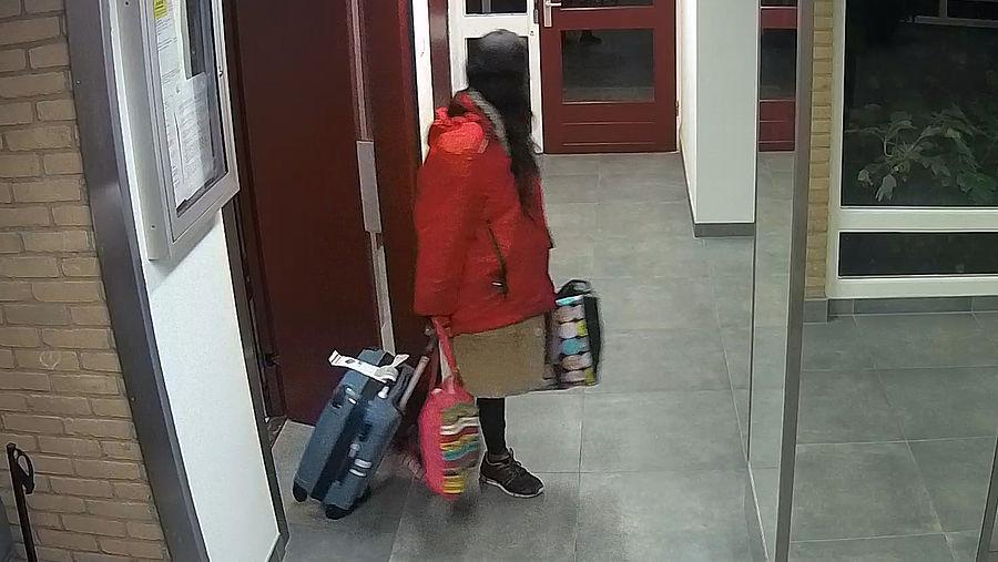 Patricia met bagage in hal flatgebouw